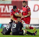 Scarlets flanker James Davies is tackled by Munster duo Denis Hurley and BJ Botha Credit: ©INPHO/Paul Jenkins