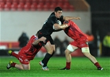 Munster out-half Ian Keatley is tackled by the Scarlets' international tighthead Samson Lee during the first half Credit: ©INPHO/Ian Cook